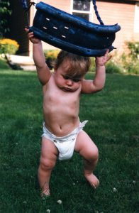 Picture of me as a baby in a diaper, pushing the seat of a swing over my head.